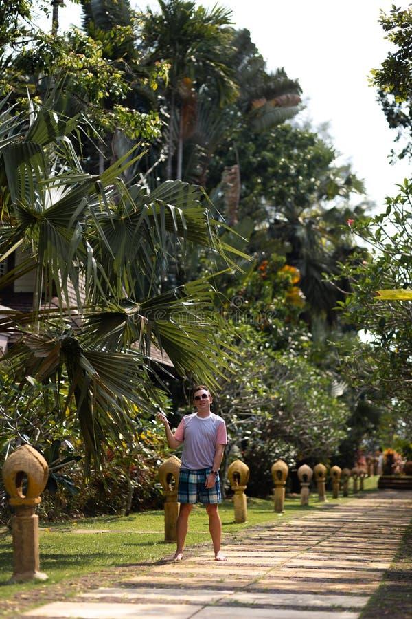 Travaler de jeune homme marchant en parc de paume sur Ko Chang, la meilleure destination de voyage de la Thaïlande en avril 2018  image libre de droits