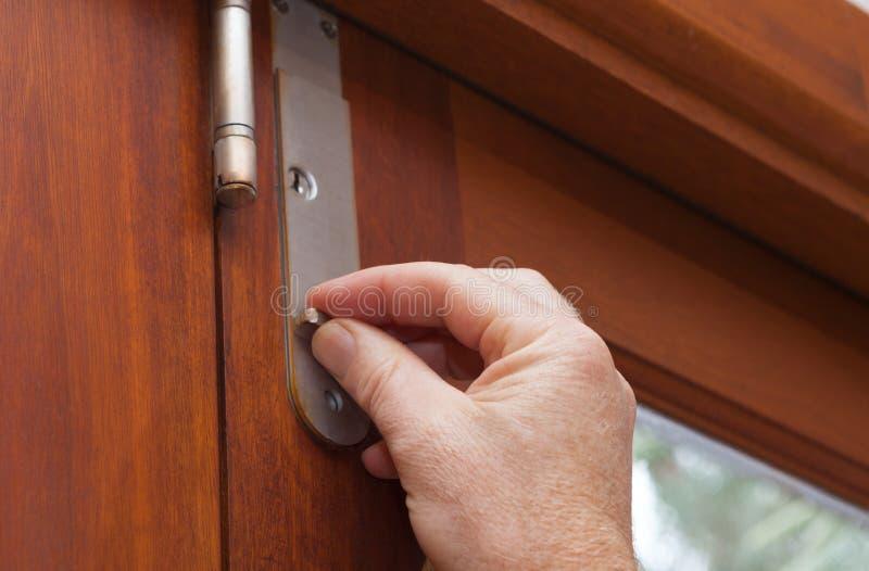 Travando a porta para manter seu casa ou escritório segura e fixe imagem de stock royalty free