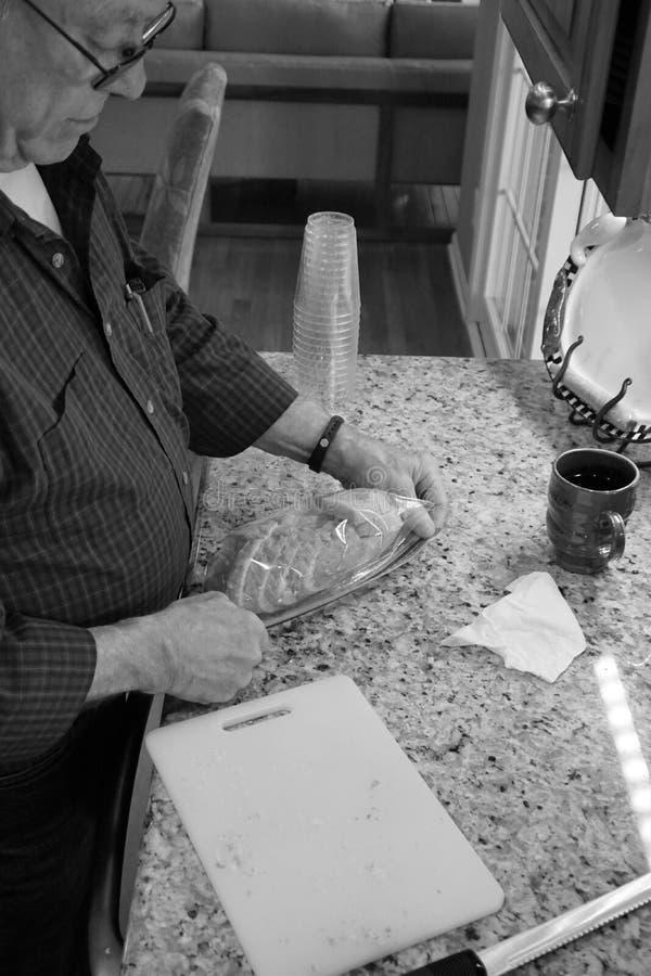 Travaux d'homme plus âgé dans la cuisine images libres de droits