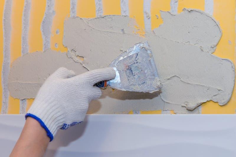 Travaux de construction étendant la tuile sur le mur image stock