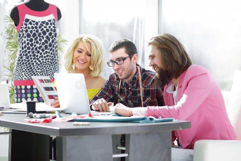 Travaux de groupe de concepteur sur un ordinateur portable dans un bureau créatif photos stock
