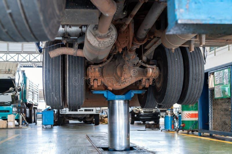Travaux de mécanicien avec le réducteur à axe arrière de la station service d'entretien de camion photos stock