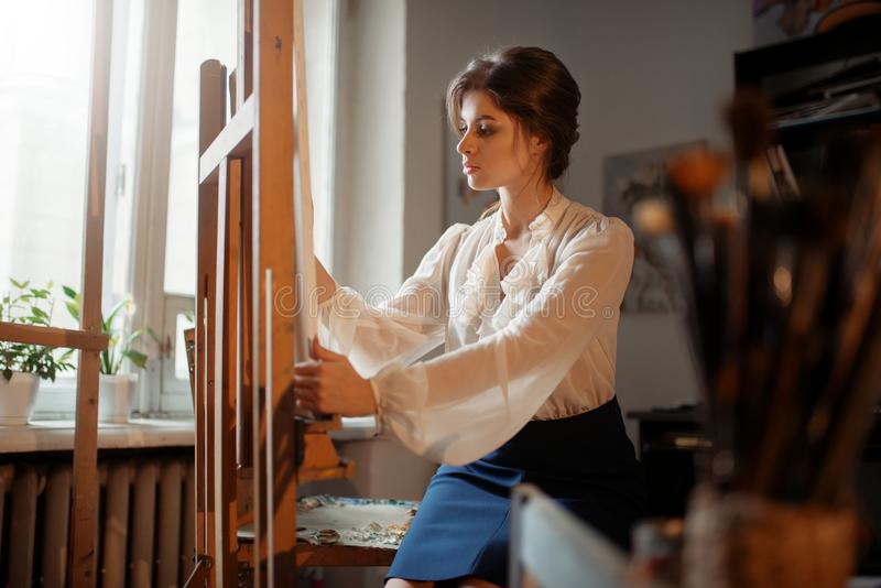 Travaux femelles d'artiste au chevalet dans le studio photos libres de droits