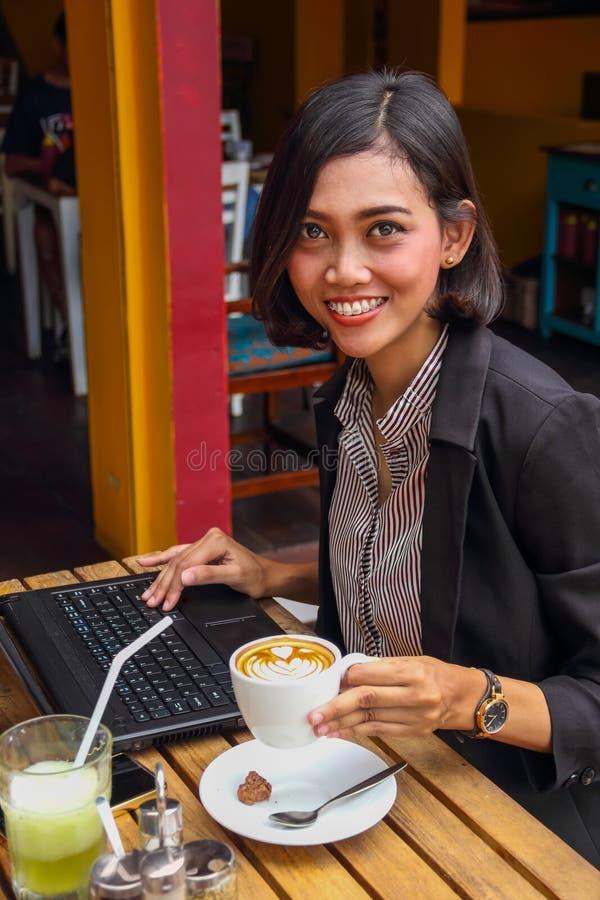 Travaux femelles réussis d'entrepreneur dehors, tenant une tasse de café photographie stock