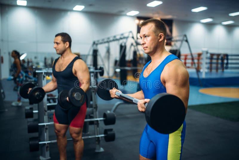 Travaux masculins forts d'athlètes avec des poids dans le gymnase photo libre de droits