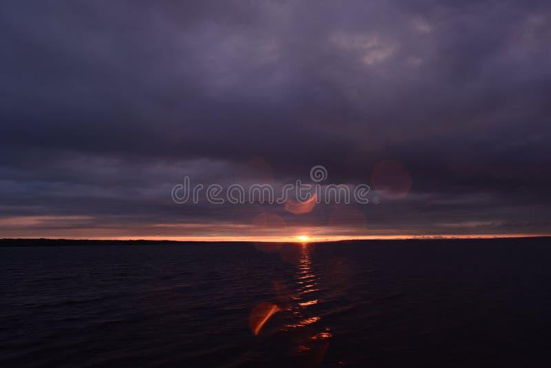 Trave solare nel cielo all'orizzonte sopra la superficie del lago d'acqua proveniente da una nuvola di tuono scura al tramonto immagine stock libera da diritti
