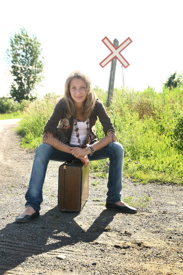 Travel. Single teenager girl sit on a old luggage on a desert road with a rail sign in background stock images