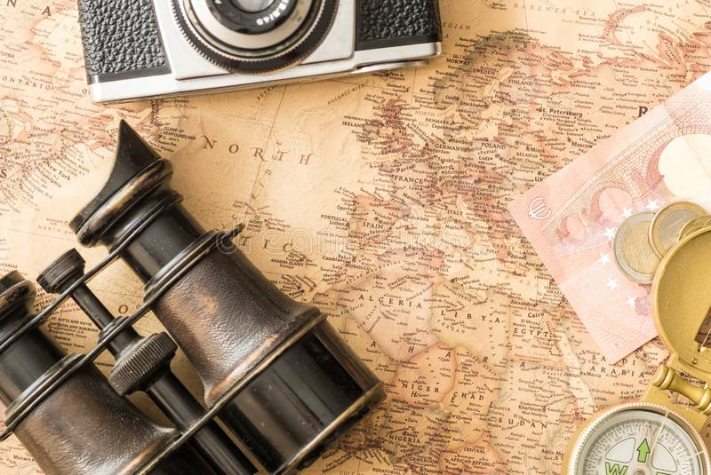 Travel accessories binoculars, compass on old, antique Europe map royalty free stock image