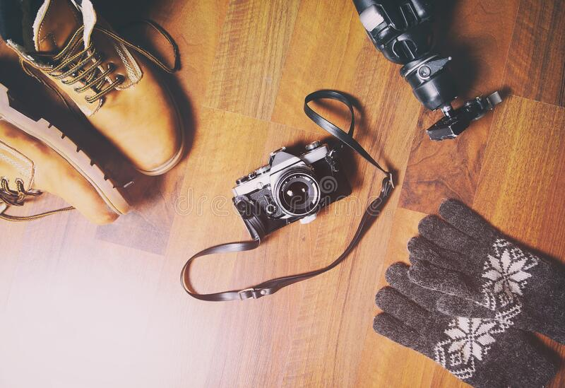 Travel accessories set on wooden background: hiking leather boots, vintage camera, tripod . stock image