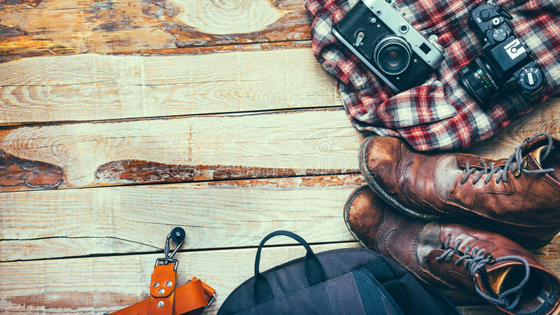 Travel accessories set on wooden background with space: old hiking leather boots, backpack, vintage film camera and shirt travel L royalty free stock photography