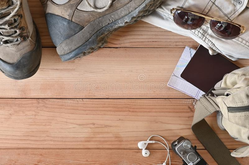 Travel accessories set on wooden desk hiking boots, jacket, backpack, map, camera and sunglasses with copy space.  stock photography