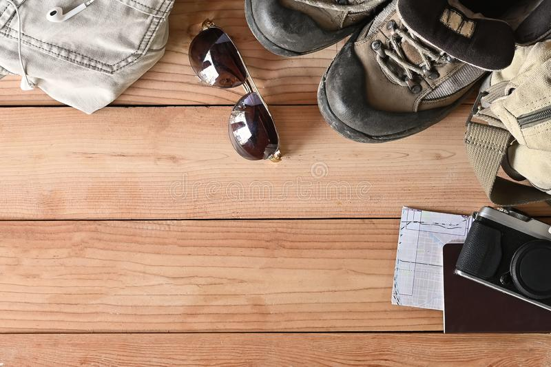 Travel accessories set on wooden desk hiking boots, jacket, backpack, map, camera and sunglasses with copy space.  royalty free stock images