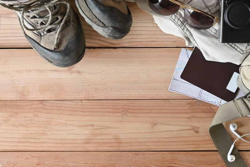 Travel accessories set on wooden desk hiking boots, jacket, backpack, map, camera and sunglasses with copy space.  royalty free stock photo