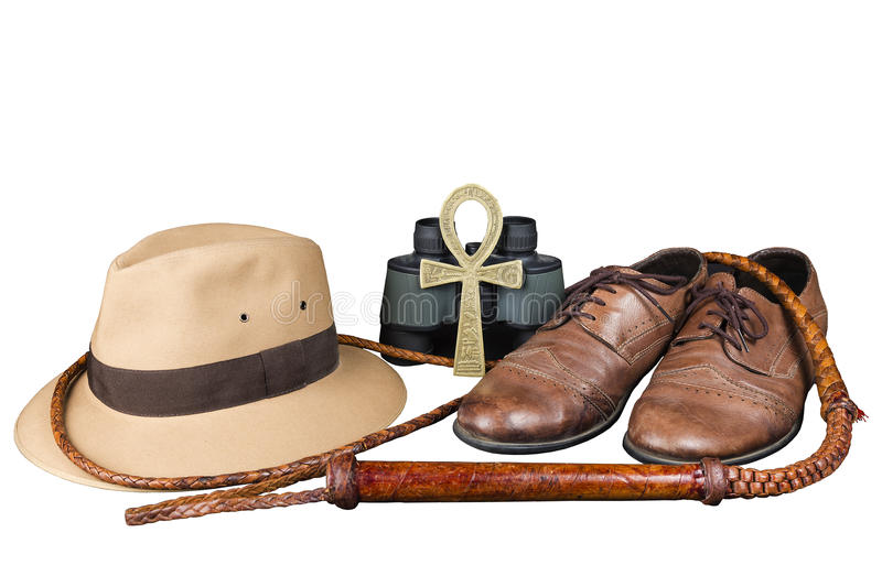 Travel and adventure concept. Vintage brown shoes with fedora hat, bullwhip, binoculars and key of life ankh isolated royalty free stock photo