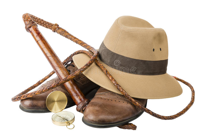 Travel and adventure concept. Vintage brown shoes with fedora hat, bullwhip and compass isolated royalty free stock photos