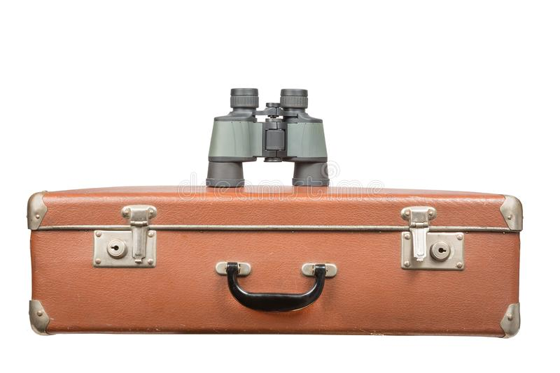 Travel and adventure concept. Vintage brown suitcase with binoculars isolated on white stock image