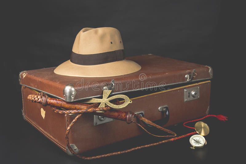 Travel and adventure concept. Vintage brown suitcase with fedora hat, bullwhip, compass and ankh key of life on dark background royalty free stock image