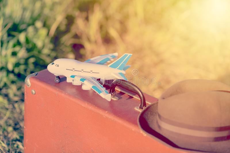 Travel and adventure concept. Vintage brown suitcase and hat with toy airplane in the green field. Toned royalty free stock image