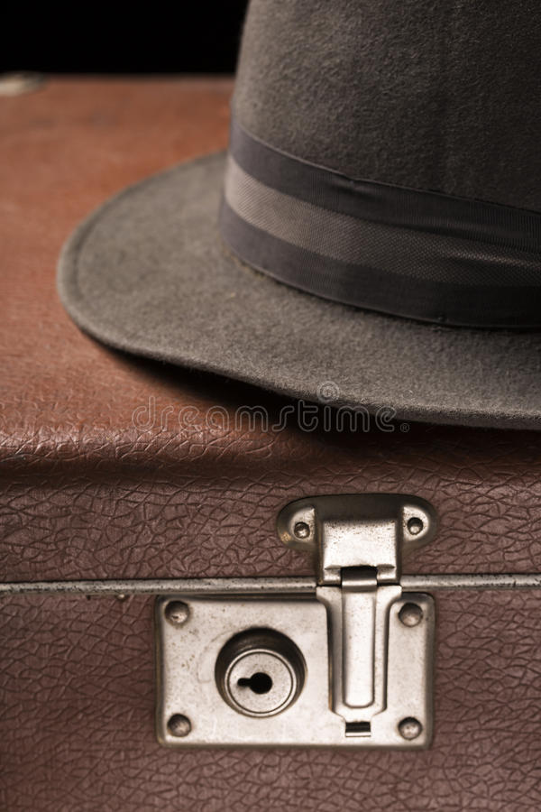 Travel and adventure concept. Vintage brown suitcase with vintage hat on black background stock image