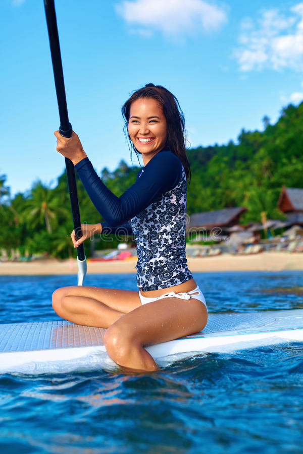 Travel Adventure. Woman Paddling On Surfing Board. Recreation, W. Travel Adventure. Beautiful Fit Woman Paddling On ( SUP, Surfing ) Board In Sea At Resort stock photo