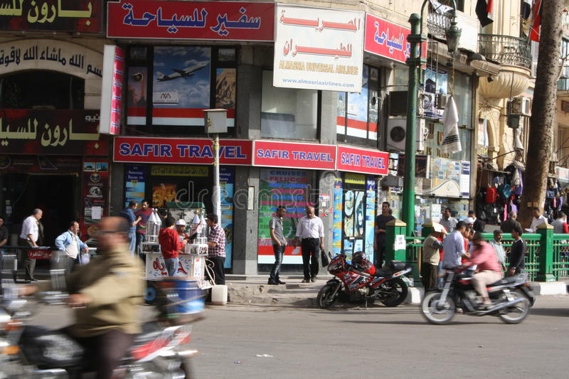 Travel agencies in downtown tahrir, Cairo Egypt. Shops, travel agencies, people waitinf for bus and cars in downtown tahrir, Cairo Egypt sellers, people walking royalty free stock image