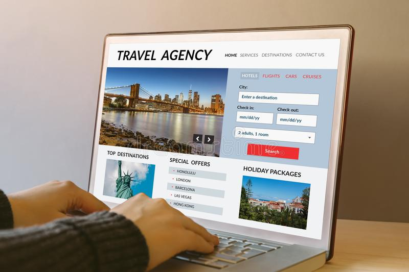 Travel agency concept on laptop computer screen. On wooden table. Hands typing on a keyboard. All screen content is designed by me stock image