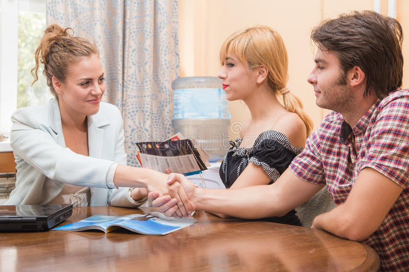 Travel agent closing a deal with two customers. Young corporate women shaking hands coming to agreement with a young couple in her office royalty free stock images