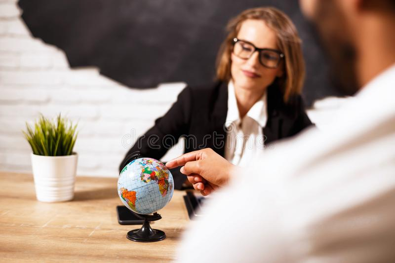 Travel Agent Proposing Hot Tours. Beautiful woman sitting at office with client and proposing hot tours to them stock image