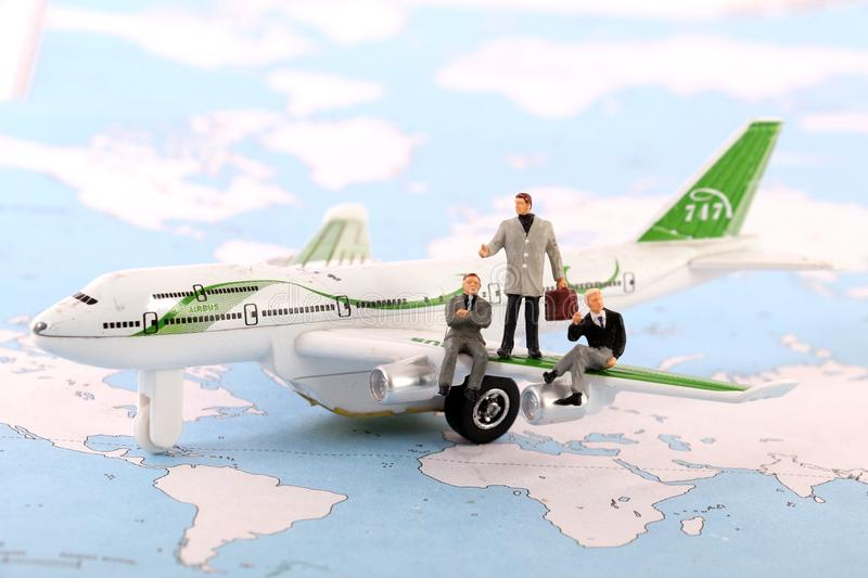 Travel agents. Beautiful shot of male figurines as travel agents sitting on plane royalty free stock photo
