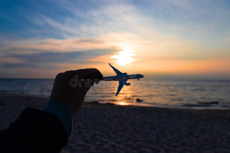 Travel and air transportation concept. Hand with small toy plane royalty free stock photo