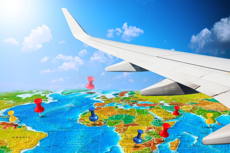 Travel by airplane around the world – globe map with pins through airplane window royalty free stock image