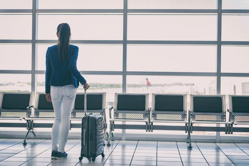 Travel airport lounge woman waiting to board plane flight to go fly on vacation. Business person looking at tarmac and airplanes. From window with suitcase royalty free stock images