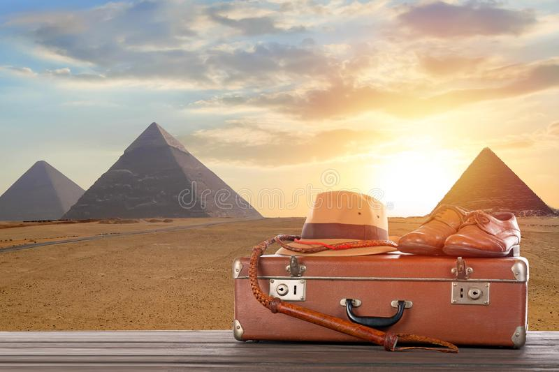 Travel, archeology and adventure concept. Vintage brown suitcase with fedora hat, bullwhip and shoes against Great pyramids in stock photos