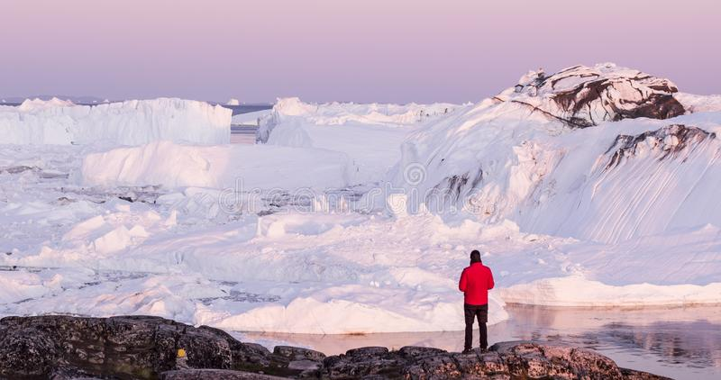 Travel in arctic landscape nature with icebergs - Greenland tourist man explorer. Tourist person looking at amazing view of Greenland icefjord - aerial drone stock photography