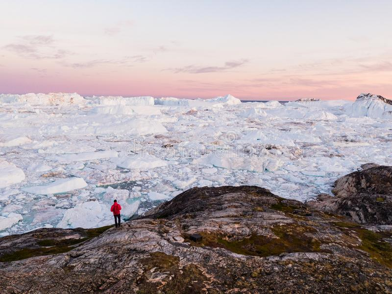 Travel in arctic landscape nature with icebergs - Greenland tourist man explorer. Tourist person looking at amazing view of Greenland icefjord - aerial drone royalty free stock images