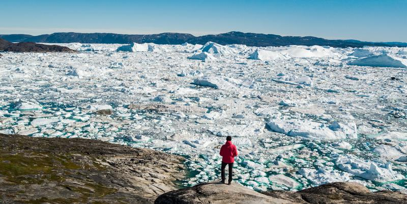 Travel in arctic landscape nature with icebergs - Greenland tourist man explorer royalty free stock image