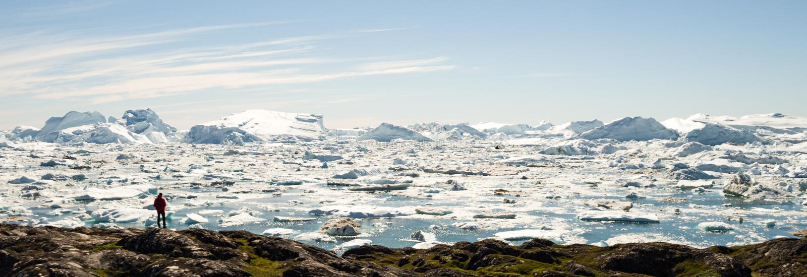Travel in arctic landscape nature with icebergs - Greenland tourist man explorer. Tourist person looking at amazing view of Greenland icefjord. Man by ice and stock photos