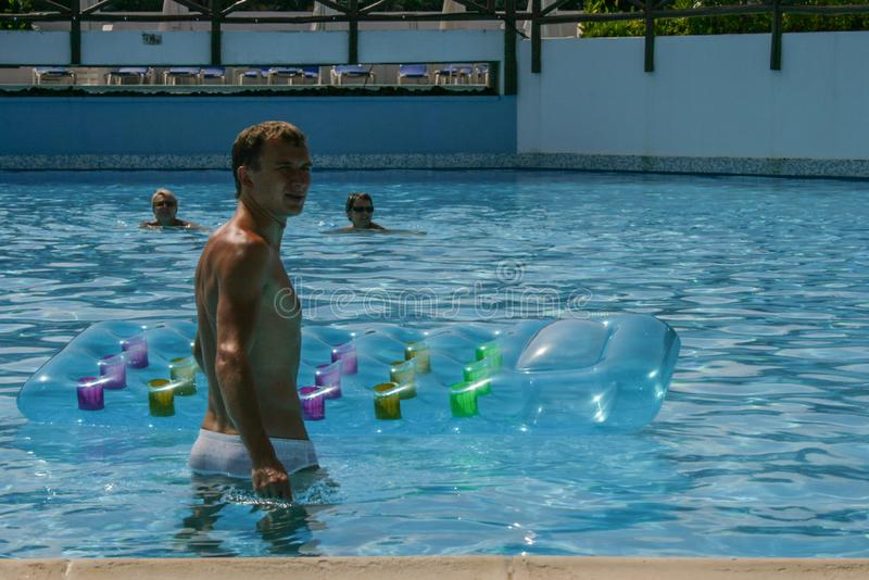 Travel around Greece. a young man swims on a water mattress in a blue water pool royalty free stock images