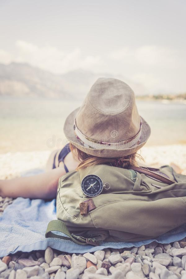 Free Travel Around The World: Compass In Foreground, Beautiful Girl With Straw Hat Lying On The Beach In The Background Stock Photography - 148220952