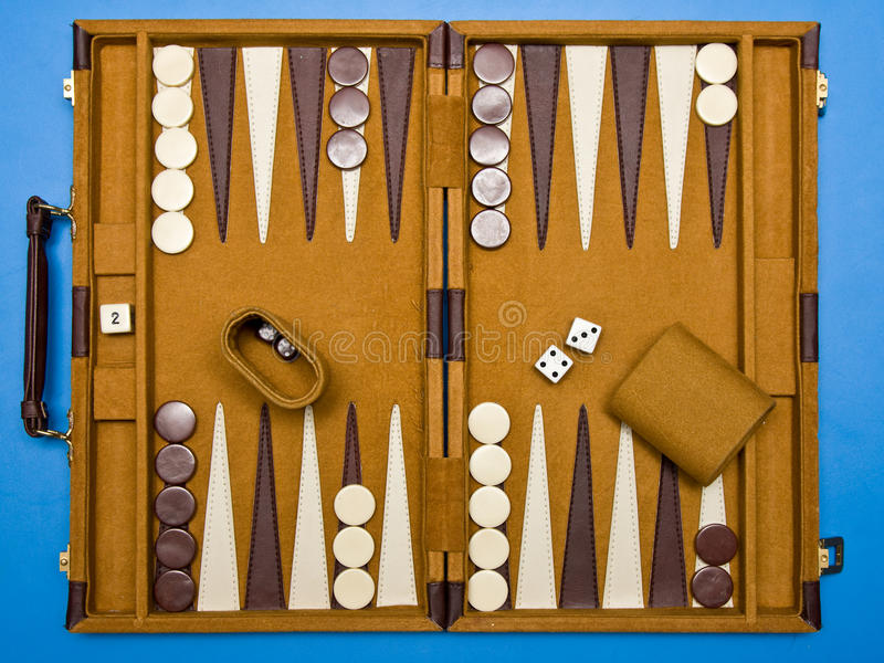 Travel backgammon. Set open and set up on blue background stock photo