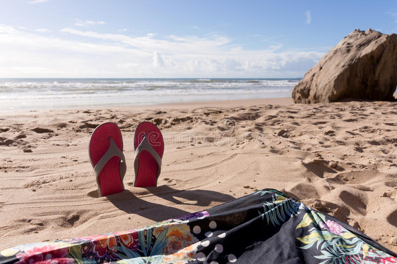 Travel background with a pair flip flops in the sand royalty free stock photo