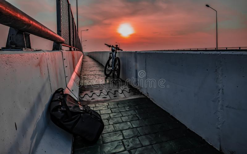 travel backpack on bicycle street with beautiful sunrise stock images