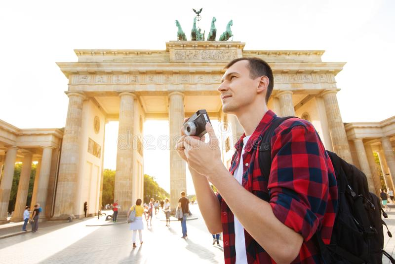 Travel in Berlin, tourist man with camera in front of Brandenburg Gate, Berlin, Germany.  royalty free stock photography