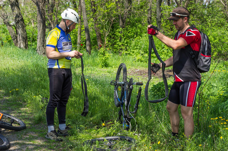 Travel by bike. Young people are being repaired tire mountain bike royalty free stock image