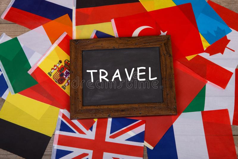 """Travel - blackboard with text """"Travel"""", flags of different countries on wooden background. Travel time - blackboard with text """"Travel"""", flags stock photos"""