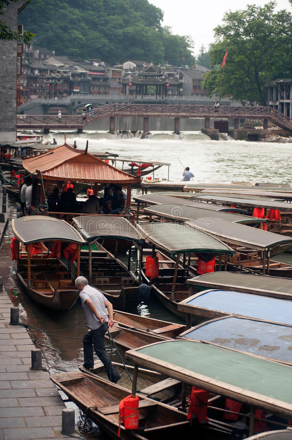 Travel boat waiting passenger in Fenghuang ancient city. Fenghuang, China - June 9,2015 : Traditional boat waiting tourists in the river at Fenghuang ancient stock images