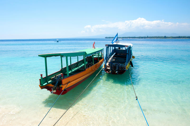 Travel boats on tropical island beach, Indonesia. Traditional exotic boats parking on clear tropical water beach on Gili Meno island. Gili Islands, Indonesia stock image