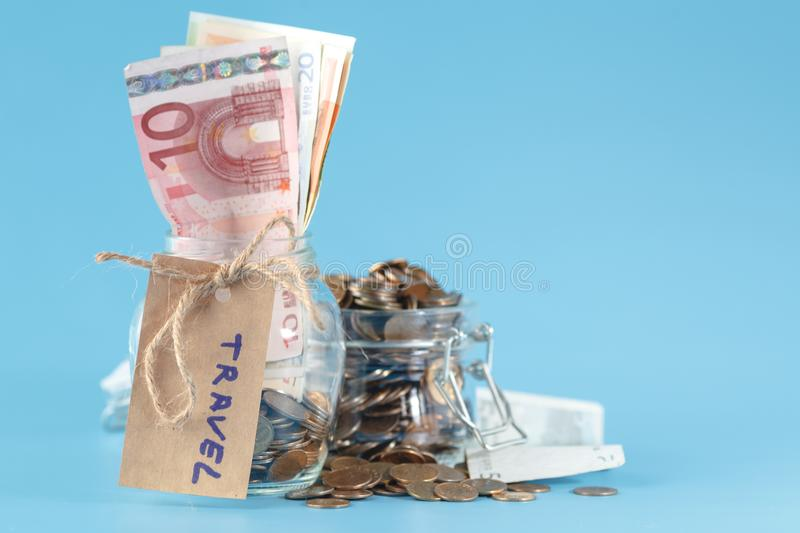 Travel budget concept. Travel money savings in a glass jar royalty free stock image
