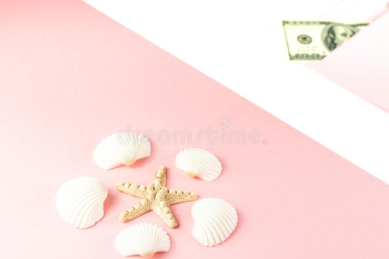 Travel budget. Money in a pink envelope, starfish, seashells on a blue background. Copy space, top view. Travel budget. Money in a pink envelope, starfish royalty free stock images