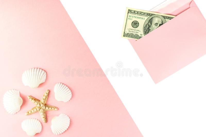 Travel budget. Money in a pink envelope, starfish, seashells on a blue background. Copy space, top view. Travel budget. Money in a pink envelope, starfish royalty free stock photo